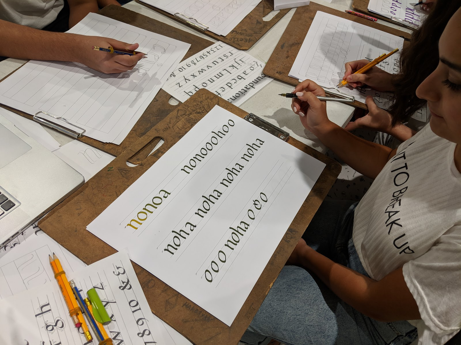 Overhead photo showing a female student practicing lettering.
