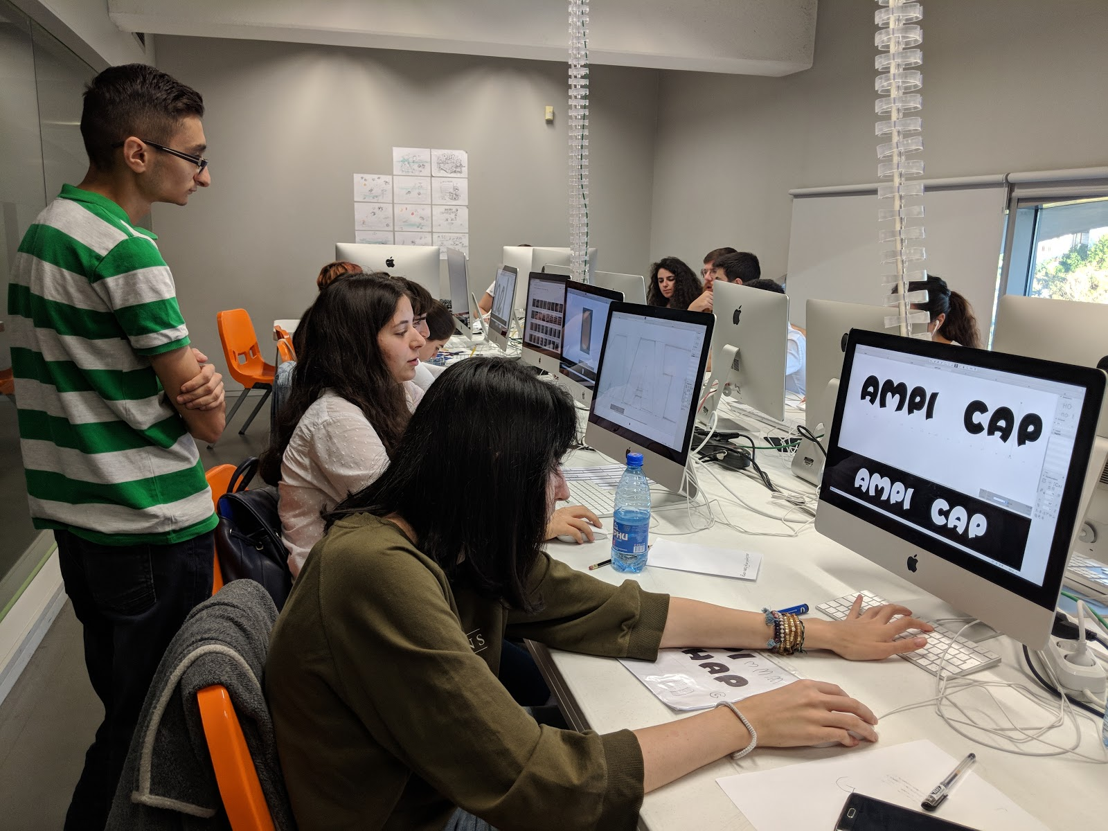 Photograph of several students working in the computer lab, after bringing their drawings into Adobe Illustrator.