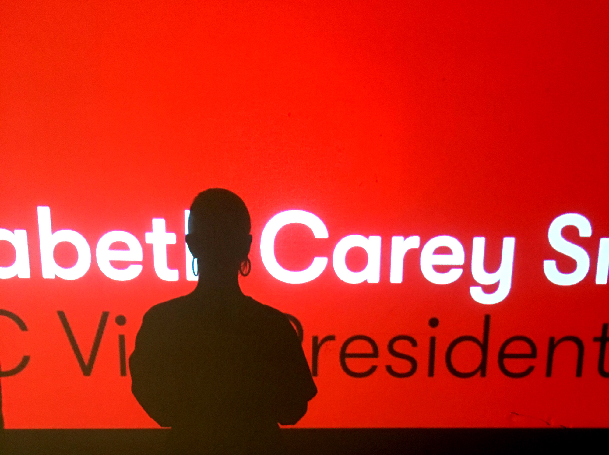 Self-portrait photograph of Elizabeth Carey Smith facing a projection screen displaying her name